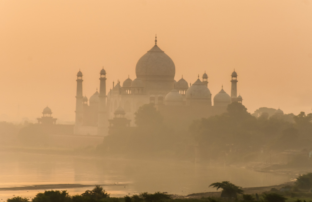 The Taj Mahal seen through the early morning mist of the river at sunrise, Agra, India.