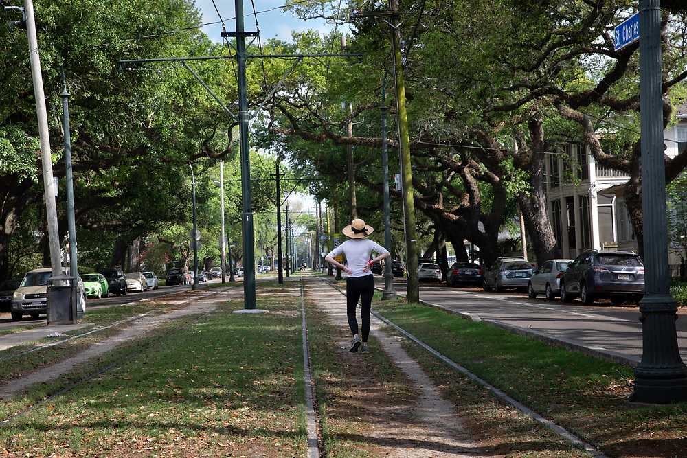 Woman walking along on the streetcar tracks along St. Charles Ave. in New Orleans where there is a stay-at-home order due to the coronavirus pandemic.