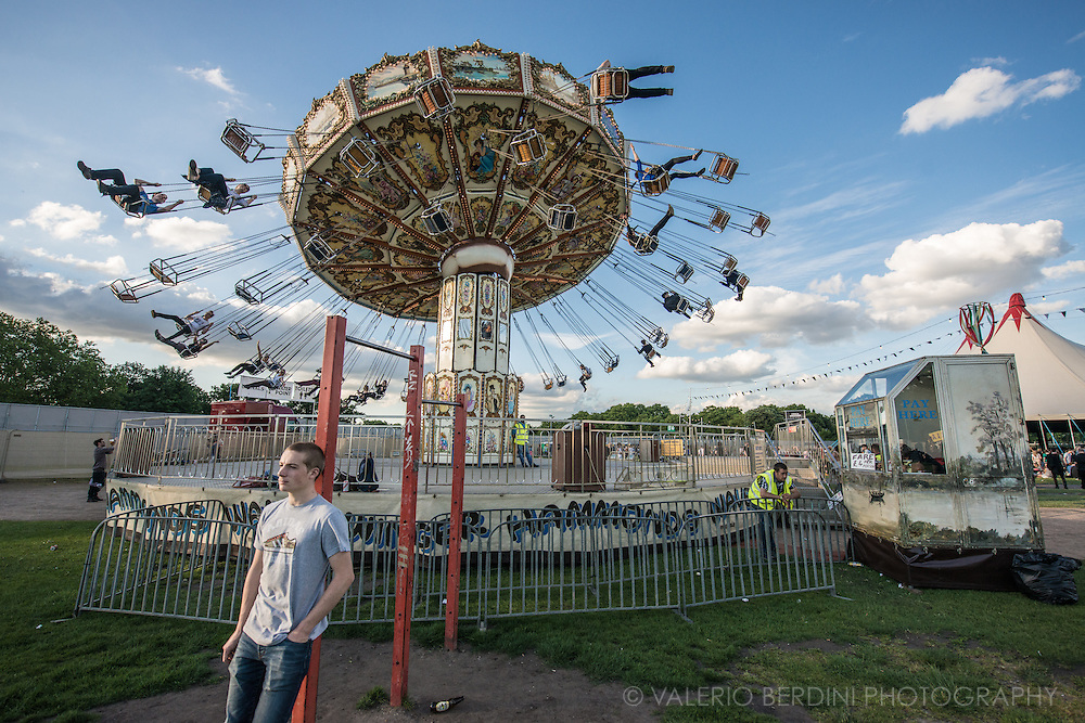 A guy waits under the Field Day carousel on day one of the East London festival in Victoria Park.
