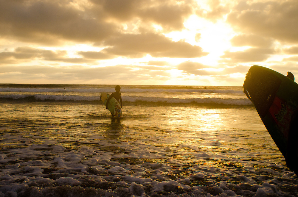 Surfers coming in at the end of the day on the beach in Montañita, Ecuador.