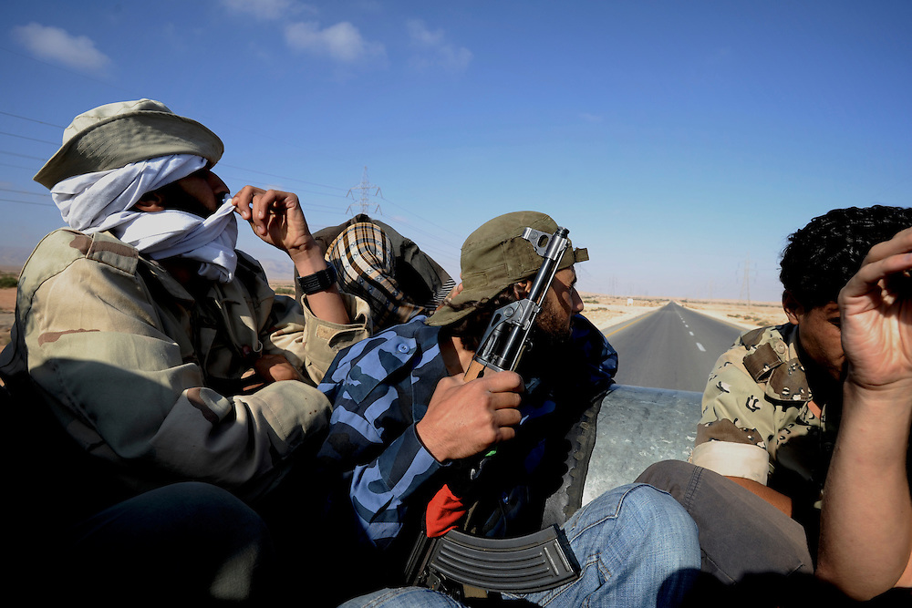 A group of Libyan rebels travel on the back of a van to the frontline in the outskirts of Bir Ghanam, where the revolutionary troops advanced on the strategic city of Zawiya taking control of several villages in the outskirts of the city.
