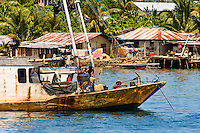 Traditional fishing boat in a water village, Manokwari, West Papua, Indonesia. Manokwari is a small town on the north east coast of the Bird's Head Peninsula, West Papua, Indonesia.  Its harbour has many wrecks from WWII.