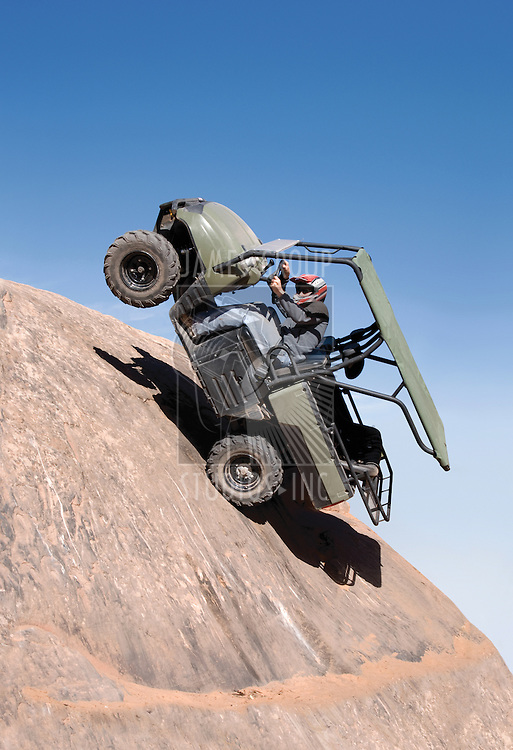 Offroad vehicle climbing up a sheer cliff and falling backwards