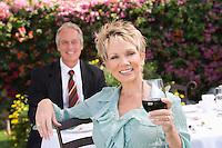 Couple drinking wine outdoors, portrait