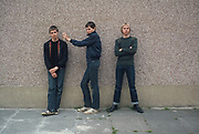 Three teenage friends in front of a pebble dashed wall with aerosol can in 1980. London, Greenford, UK, 1980s.