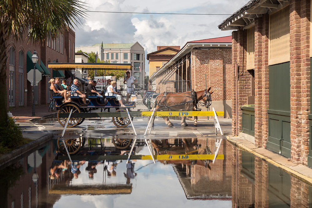 A horse drawn tourist carriage passes a street closed from flooding at the old City Market in downtown historic district September 30, 2015 in Charleston, SC. Hurricane Joaquin is bringing high surf, heavy rain and flooding to the lowcountry as it passes slowly in the Atlantic Ocean.