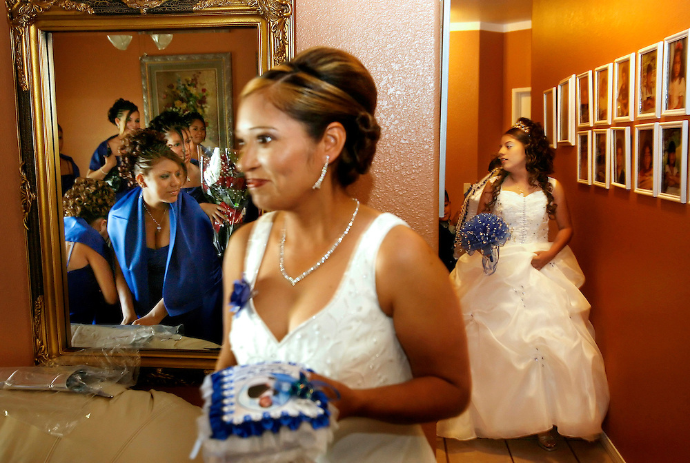 Martha Ureña enters the living room before her daughter, Elizabeth Ureña, as the damas eagerly await to see her dressed up for her quinceañera.