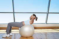 Woman Doing Sit-Ups on exercise ball in gym