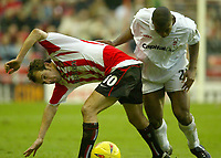 Photo. Andrew Unwin.<br /> Sunderland v Nottingham Forest, Nationwide League Division One, Stadium of Light, Sunderland 10/01/2004.<br /> Sunderland's Marcus Stewart (l) twists and bends with Forest's Wes Morgan (r).