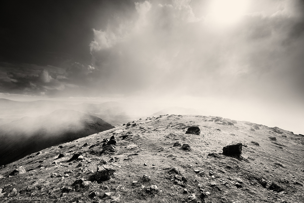 """It's August, it looked sunny. The hills are swarming with summer walkers, like mozzys on a sweaty cow. I have to go further and further afield at this time of year to escape the vortex desperation of lemmings sucked towards the highest peaks. Arenig Fawr jumped out at me on the map - The description: """"To some, the poor Southern relative of the Snowdonia bigger peaks"""" - but to me exactly the reason to reach for it's summit. The downside to these hills, is that their very disuse means the paths are not so precise, so trodden or so scarred. Map reading and navigation are worthwhile skills but even with my OS 1:25,000 the description of the descent as, 'follows faint, sometimes invisible paths, across boggy vegetated hillsides"""" did worry me a little, especially as the clouds were already thickening over Snowdonia by the time we'd even reached Capel Curig!"""