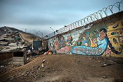 NO WEB/NO APPS - (Text available) Murals made by the population of Pamplona Alta against discrimination on the 'Wall of shame' (Muro de la Verguenza) which divides the Districts of Santiago de Surco and San Juan de Miraflores, in the city of Lima, Peru in May 2017. In Peru's capital Lima, a three-meter-high concrete wall topped with reels of razor wire separates two areas. The so-called 'Wall of Shame' - sometimes nicknamed 'Peru's Berlin Wall' - divides the urbanisation of Las Casuarinas, where some of the country's richest inhabitants live, and the poor suburb of Vista Hermosa next door. It was initially put up over fears that the inhabitants from the poor neighbourhood would steal from wealthy fellow citizens living nearby. On the rich side of the wall, the price for a square meter can exceed 2,000 dollars. To enter the area, you must show your ID to the guards watching the gate at the bottom of the hill. Former high-ranking politicians and bank directors live here. Their houses are surrounded by lush gardens and swimming pools despite the scarcity of water. Meanwhile, on the San Juan de Miraflores side, residents often fall victim to robbery and theft. They live in houses of barely 25m², made from scrap material, surrounded by the sand and earth characteristic of Lima's desert landscape. Photo by Giacomo D'Orlando/ABACAPRESS.COM