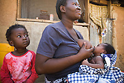 A girl sits next to her mother with she breastfeeds her other child. Northern Ghana, Thursday November 13, 2008.