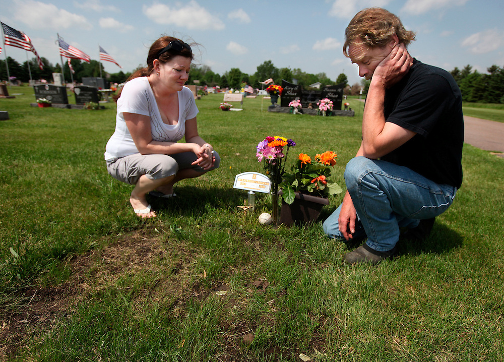 Camille and Paul Cressman grieve by the grave of their 17-year-old son, Kendall, at the Brandon Cemetery. Kendall fell to his death from the three-story Brandon Elementary school on May 9, 2011 after ingesting over-the-counter dextromethorphan (DM) cough suppressant medications. His parents are campaigning to reduce access to medicines that some teens abuse.