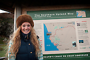 Young woman with long blonde hair and a furry brown hat lsmiles at camera in front of tourist information board, Portpatrick, Southern Upland Way