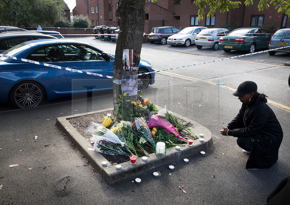 © Licensed to London News Pictures. 08/10/2016. London, UK. A woman looks at tributes placed near the scene of a shooting in Eastney Road, Croydon. Police were called to reports of a man suffering a gunshot wound at 11.30 PM on Friday night. Officers from the Homicide and Major Crime Command are investigating after the man was pronounced dead at the scene.Photo credit: Peter Macdiarmid/LNP