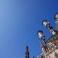 Brilliant spring blue skied day in Brugge in the Grand Place - a modern day lamp post styled to blend in with the medieval buildings of the city as the penultimate marker of the 21st century flies overhead - this city has always been a crossroads for people since the mid 1200s!