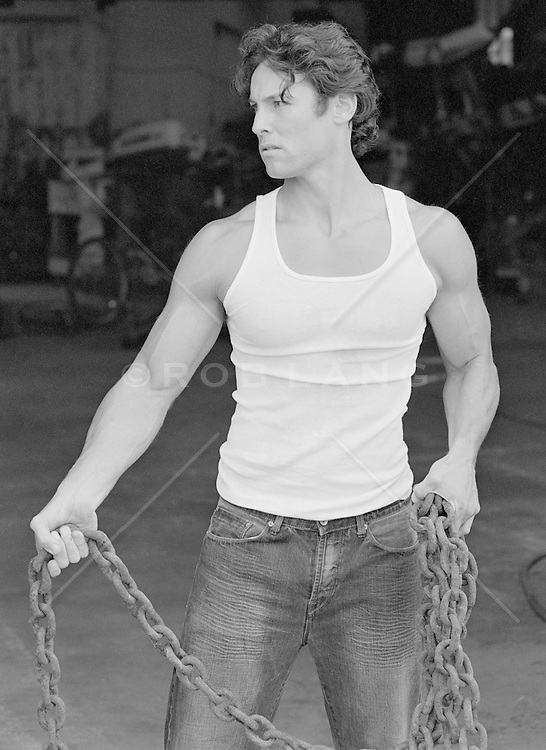 hot man holding a large chain in a garage