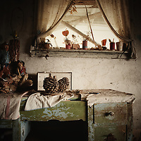 Old, peeling dressing table under window in old dilapidated house.