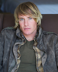 portrait of a handsome young man with long blond hair and blue eyes