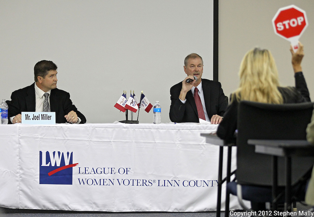 """Republican candidate for auditor Garth Fagerbakke (R) finishes answering a question as the timekeeper raises the """"stop sign"""" as Auditor Joel Miller (D) listens at the Linn County Auditor Candidate Forum sponsored by the League of Women Voters Linn County at Kirkwood Training and Outreach Center, 3375 Amar Drive, in Marion on Tuesday, October 23, 2012."""