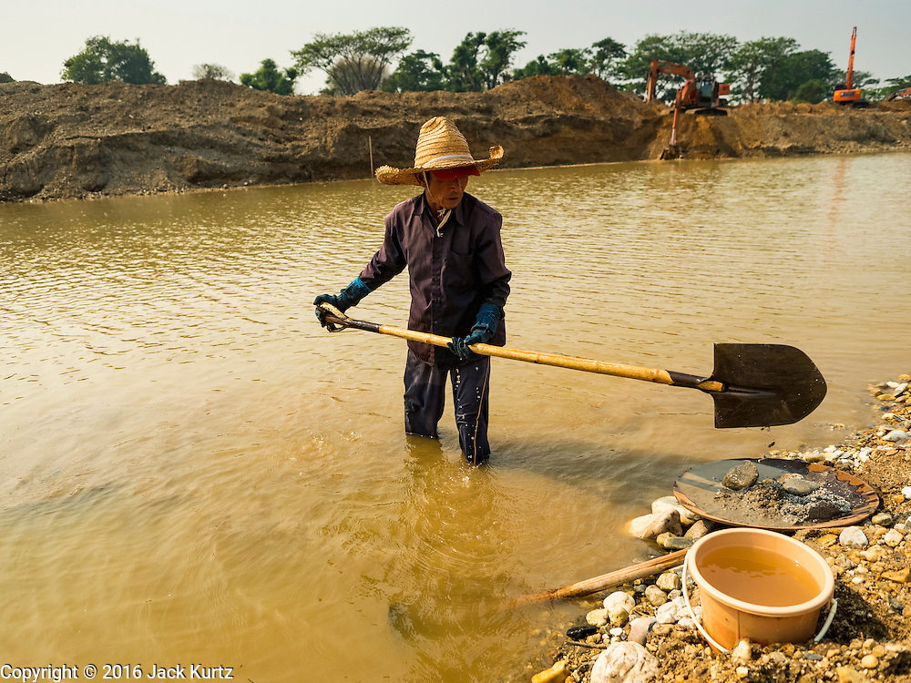 "01 APRIL 2016 - WANG NUEA, LAMPANG, THAILAND:  A man panning for gold shovels rocks and gravel into his pan in the Mae Wang. Villagers in the Wang Nuea district of Lampang province found gold in the Mae Wang (Wang River) in 2011 after excavation crews dug out sand for a construction project. A subsequent Thai government survey of the river showed ""a fair amount of gold ore,"" but not enough gold to justify commercial mining. Now every year when the river level drops farmers from the district come to the river to pan for gold. Some have been able to add to their family income by 2,000 to 3,000 Baht (about $65 to $100 US) every month. The gold miners work the river bed starting in mid-February and finish up by mid-May depending on the weather. They stop panning when the river level rises from the rains. This year the Thai government is predicting a serious drought which may allow miners to work longer into the summer. The 2016 drought has lowered the water level so much that the river is dry in most places and people can only pan for gold in a very short stretch of the river.     PHOTO BY JACK KURTZ"