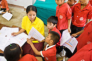 "19 FEBRUARY 2008 -- SANGKLABURI, KANCHANABURI, THAILAND: Second grade Burmese refugee students study English at Baan Unrak School in Sangklaburi, Thailand. The school's curriculum is in taught in Thai but the children start studying English in second grade. Baan Unrak children's home and school, established in 1991 in Sangklaburi, Thailand, gives destitute children and mothers a home and career training for a better future. Baan Unrak, the ""Home of Joy,"" provides basic needs to well over 100 children, and  abandoned mothers. The home is funded by donations and the proceeds from the weaving and sewing shops at the home. The home is a few kilometers from the Burmese border. All of the women and children at the home are refugees from political violence and extreme poverty in Burma, most are Karen hill tribe people, the others are Mon hill tribe people. The home was started in 1991 when Didi Devamala went to Sangklaburi to start an agricultural project. An abandoned wife asked Devmala to help her take care of her child. Devmala took the child in and soon other Burmese women approached her looking for help.    Photo by Jack Kurtz"
