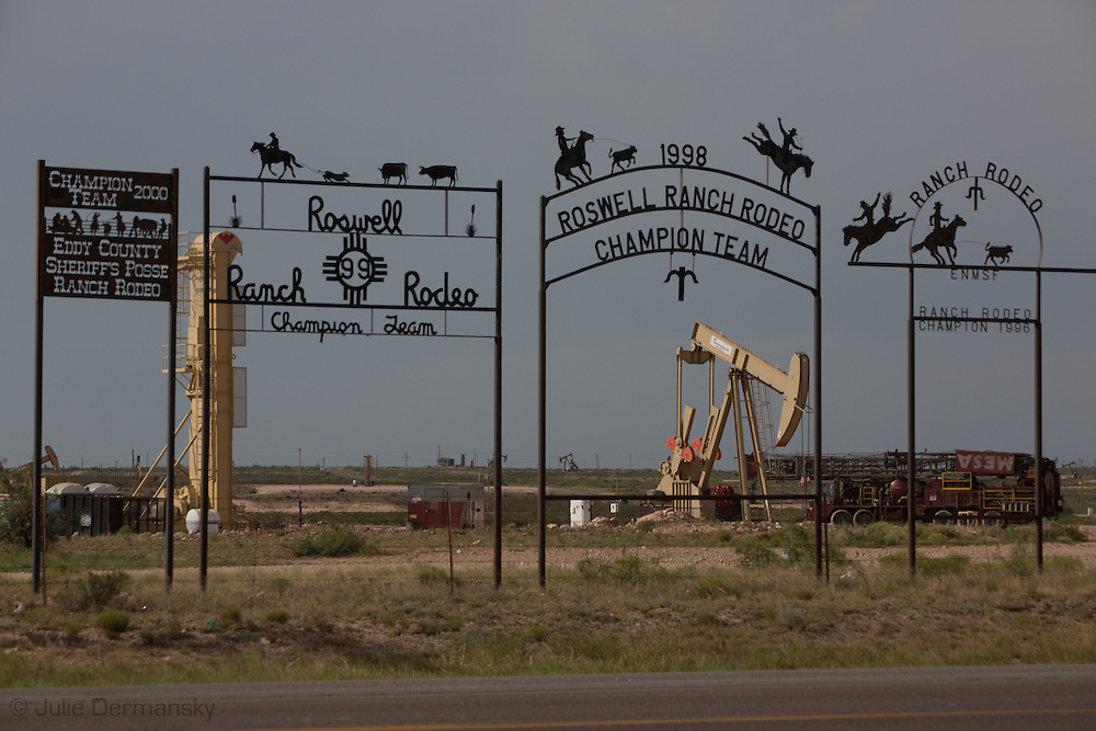 Wrought iron signs in front of  fracking industry installations as far as the eye can see in Eddy County New Mexico. <br /> Eddy County's oil patch in the Permian Basin is experiencing an oil boom due to the fracking industry.