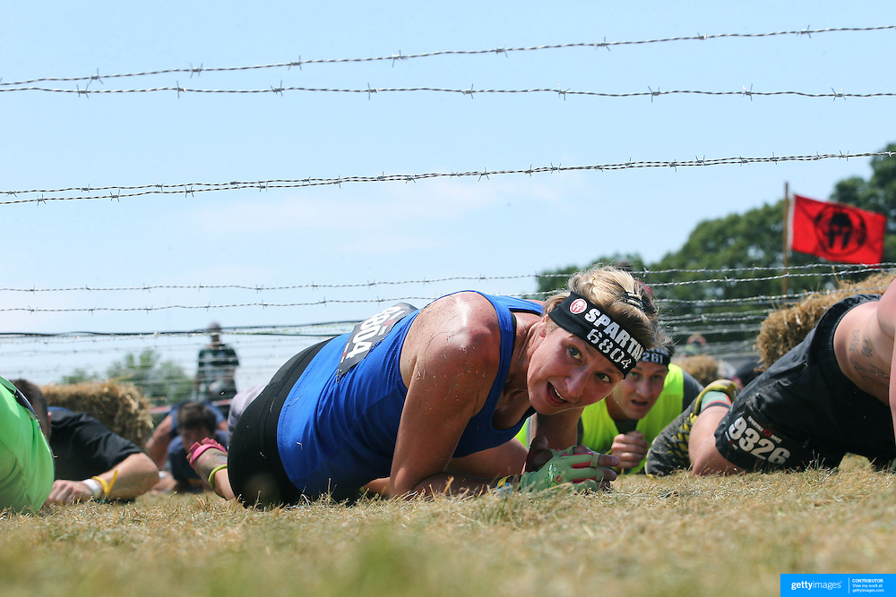 Charleen Collins in action at the barbed wire crawl obstacle during the Reebok Spartan Race. Mohegan Sun, Uncasville, Connecticut, USA. 28th June 2014. Photo Tim Clayton