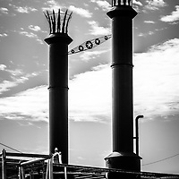 Steamboat smokestacks black and white picture. The smoke stacks are on the Natchez steam boat in New Orleans. The Natchez Steamboat is a sternwheel paddle wheel steamer that provides cruises on the Mississippi River.