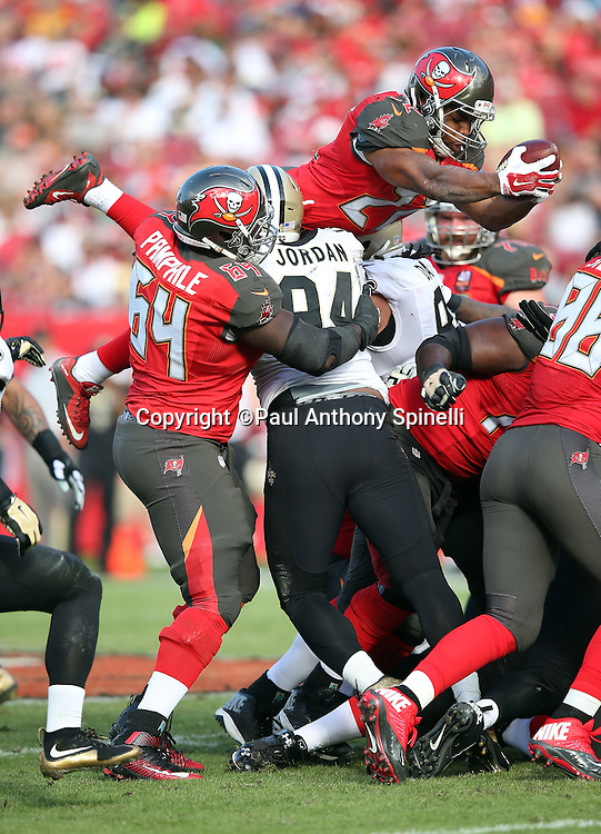 Tampa Bay Buccaneers offensive guard Kevin Pamphile (64) blocks New Orleans Saints defensive end Cameron Jordan (94) while Tampa Bay Buccaneers running back Doug Martin (22) dives over the pile for a first down on a third down play with one yard to go for a first down in the third quarter during the 2015 week 14 regular season NFL football game against the New Orleans Saints on Sunday, Dec. 13, 2015 in Tampa, Fla. The Saints won the game 24-17. (©Paul Anthony Spinelli)