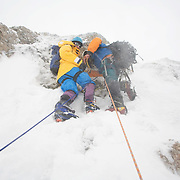 Jonathan Thompson climbs up a wind swept mountain in Antarctica with climbing guide Milton.