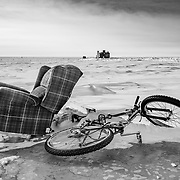 An easy chair and a mountain bike  on the Polar Plateau, with IceCube Lanoratory in the distance.