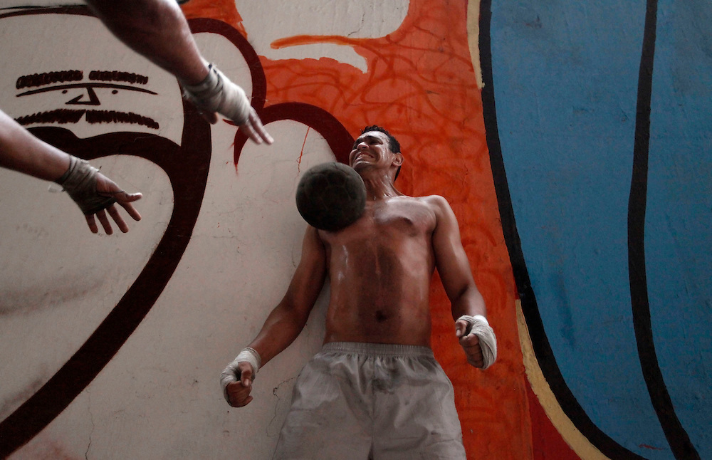 """Aspiring boxer Valdir Aparecido (nicknamed """"Gorilla"""") throws a ball at the torso of Joilson Santos (nicknamed """"Talent""""), while training at a gymnasium under the Alcantara Machado viaduct in the Mooca neighborhood of Sao Paulo, March 24, 2011. The Boxing Academy of Garrido, founded by Brazilian former pro boxer Nilson Garrido, adopts primitive training equipment that he developed himself during his years as a coach, in a project whose goal is to take the sport to the poor and marginalized population."""