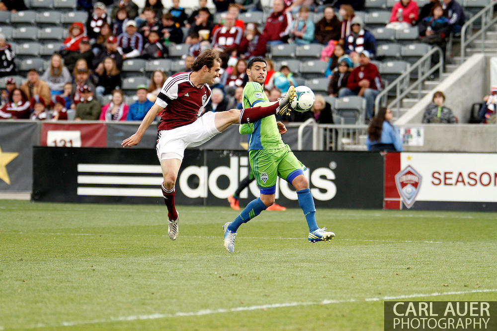 April 20th, 2013 Commerce City, CO - Colorado Rapids midfielder Brian Mullan (11) flies in to kick the ball away from Seattle Sounders FC midfielder Lamar Neagle (27) in the second half of action of the MLS match between the Seattle Sounders FC and the Colorado Rapids at Dick's Sporting Goods Park in Commerce City, CO