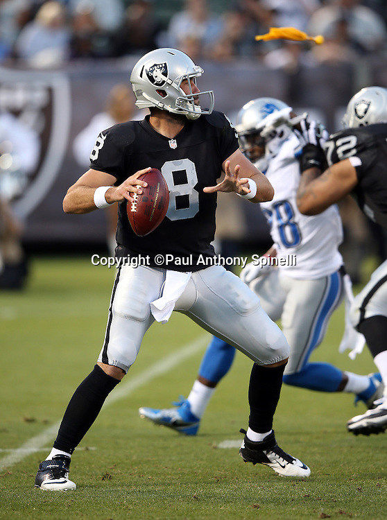 Oakland Raiders quarterback Matt Schaub (8) throws a pass as a yellow penalty flag flies past him during the 2014 NFL preseason football game against the Detroit Lions on Friday, Aug. 15, 2014 in Oakland, Calif. The Raiders won the game 27-26. ©Paul Anthony Spinelli
