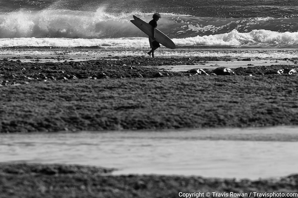 Pro surfer Rob Machado walks across the reef at Uluwatu.