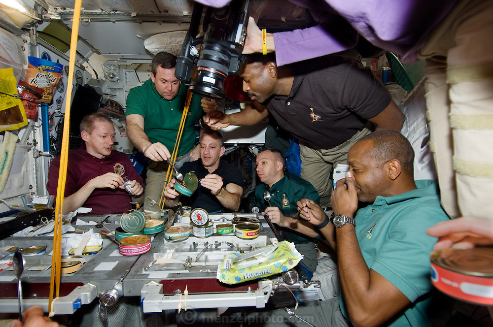 Astronauts get together for a potluck dinner in the galley of the Unity Node of the International Space Station.  (From the book What I Eat: Around the World in 80 Diets.) The crews share a meal of mostly canned treats saved for the occasion: crab, oysters, clams, tuna, mushrooms, and calf cheeks in plum sauce. MODEL RELEASED.