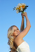 Bride holding bouquet aloft