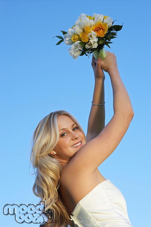Bride holding bouquet aloft