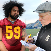 USC Starting Right Guard,  John Martinez, who has many Kaufusi relatives in the Territory of American Samoa, shares his Trojan pride with sportswriter, Dan Weber of USCFootball.com.  The USC Trojans practiced for the second day at Bishop Gorman High School in preparation for the Royal Purple Las Vegas Bowl to be held 12/21/13.  11/19/13, 4 pm, Photo by Barry Markowitz