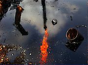 An oil flare reflects in a toxic waste pool dug by Texaco when they operated in the Ecuadorian Amazon. Hundreds of such pools are known to drain directly into the region's waterways, leading to widespread contamination.