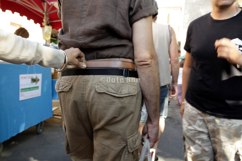 woman holding on to the belt of her male person at a crowded outdoors market