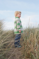 Boy (3-4) standing on path among long grass