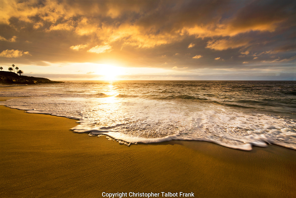 Storm clouds opened up when I took this photo of a golden Pacific Ocean sunset.  The gold colors of the cloud rise up the golden secluded beaching San Diego.