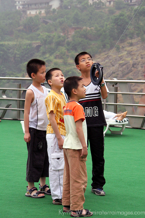 A group of Chinese boys fly a kite while cruising on the Yangtze River.