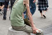 female person with anorexia symptoms resting in public pedestrian area