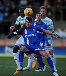 Gillingham's John Marquis is tackled by  Yeovil Town's Nathan Smith - Photo mandatory by-line: Harry Trump/JMP - Mobile: 07966 386802 - 21/02/15 - SPORT - Football - Sky Bet League One - Yeovil Town v Gillingham - Huish Park, Yeovil, England.