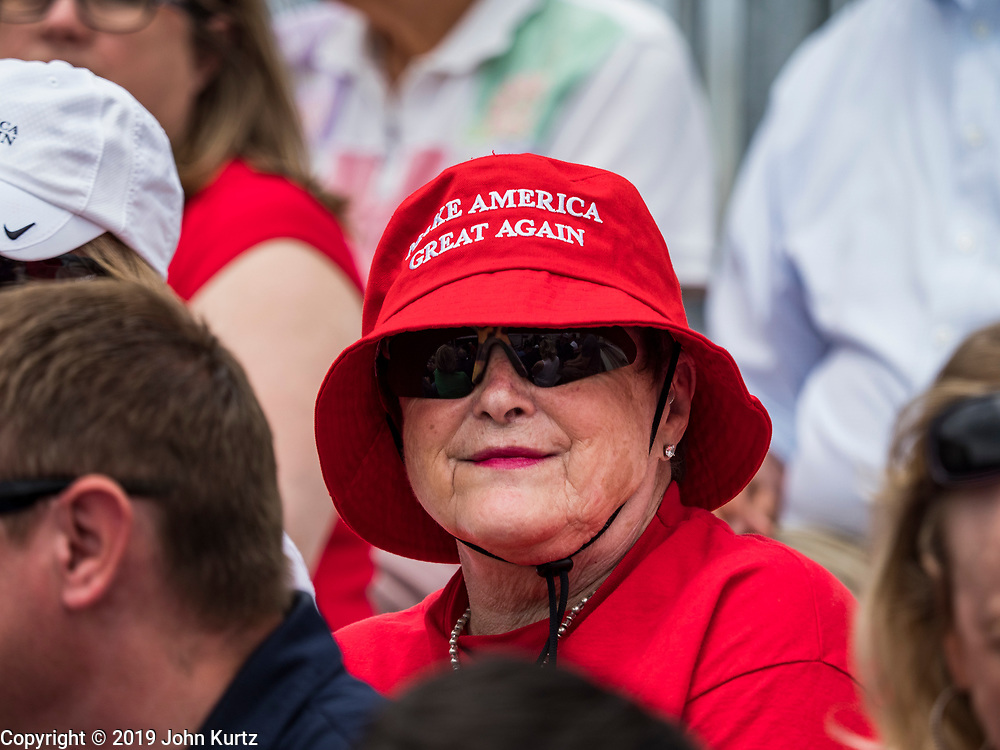 """11 JUNE 2019 - COUNCIL BLUFFS, IOWA: A woman wearing a """"Make America Great Again"""" bucket hat waits to see President Trump at Southwest Iowa Renewable Energy. President Trump visited Southwest Iowa Renewable Energy in Council Bluffs Tuesday to announce that his administration was relaxing rules on E15, an ethanol additive for gasoline. Iowa is one of the leading ethanol producers in the U.S. and Iowa corn farmers hope the administration's change in E15 rules will spur demand for corn.          PHOTO BY JACK KURTZ"""