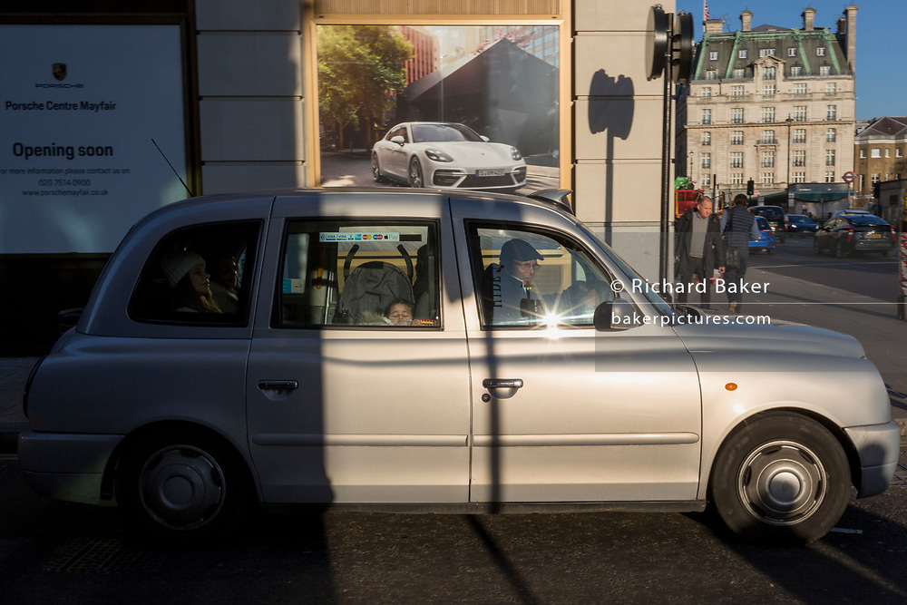 A taxi drives a family past a Porsche luxury car ad where a new dealership is due to open on the corner of Clarges Street, and Piccadilly, W1, on 20th January 2020, in London, England.