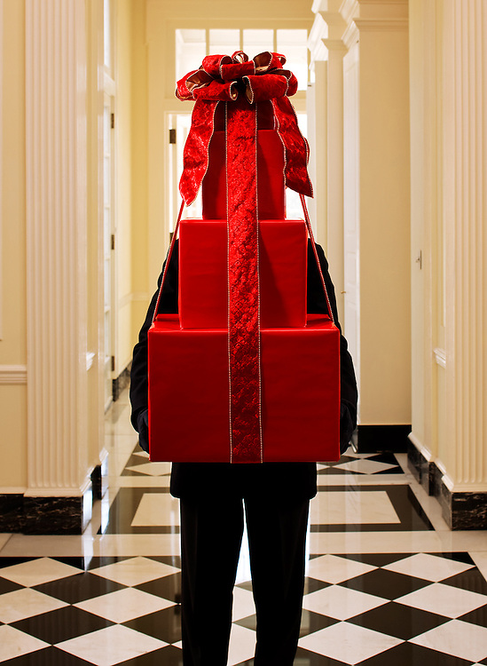 Image of a man holding three gift boxes wrapped in red wrapping paper, I mage taken in Duke Mansion in Charlotte, North Carolina.